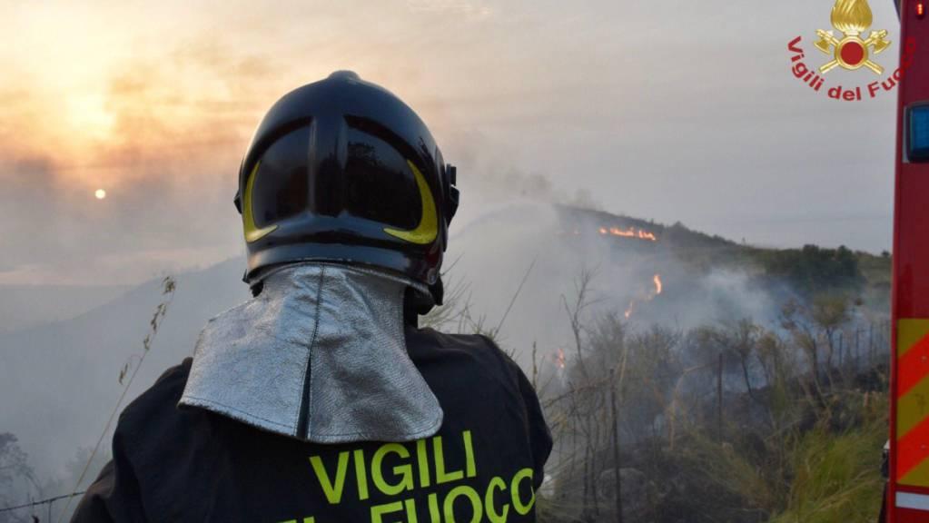 HANDOUT - Ein Feuerwehrmann steht vor einem Gebiet, in dem mehrere Brände lodern (Aufnahmeort unbekannt). Weit über 1000 Einsätze leistete die italienische Feuerwehr in den letzten 24 Stunden, um zahlreiche Waldbrände auf dem süditalienischen Festland und auf Sizilien zu bekämpfen. Foto: Vigili del Fuoco/dpa - ACHTUNG: Nur zur redaktionellen Verwendung im Zusammenhang mit der aktuellen Berichterstattung und nur mit vollständiger Nennung des vorstehenden Credits