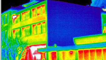 Infrarotaussenaufnahme eines Verwaltungsgebäudes mit guter Wärmedämmung an der Wandfläche (blau) und grossen Wärmeverlusten durch die Fensterfronten (rot) auf einem Wärmebild