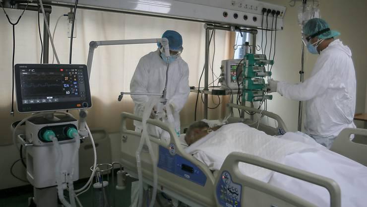 Medizinische Mitarbeiter in Schutzausrüstung versorgen einen im Bett liegenden Corona-Patienten auf der Intensivstation des Krankenhauses der Rafik-Hariri-Universität. Foto: Marwan Naamani/dpa