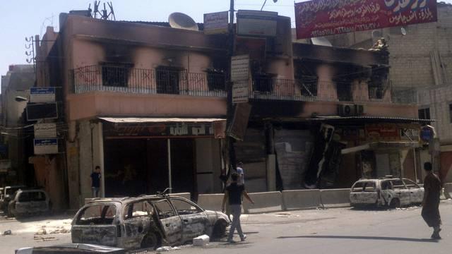 Ein Strassenzug in Damaskus mit ausgebrannten Gebäuden und Autos