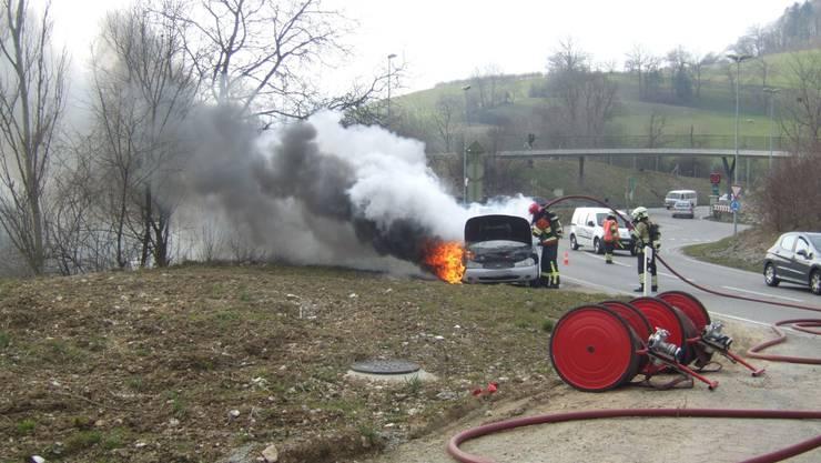 Der brennende Wagen. Die Feuerwehr ist am Löschen.