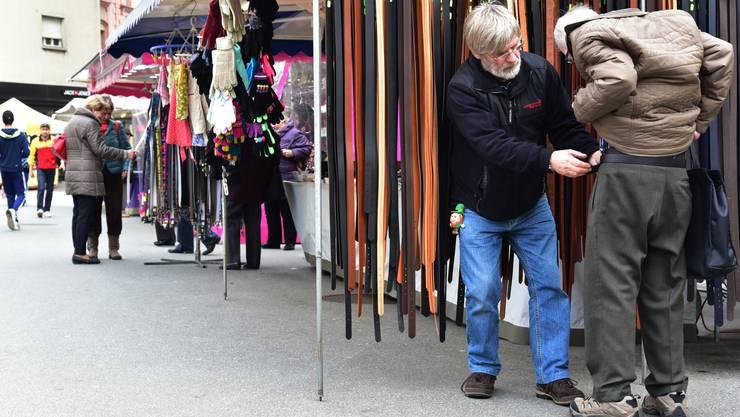 Ein Verkäufer probiert einem Kunden einen Gurt an.
