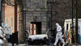 Untersuchungen am komplett zerstörten Auto in der Bishop Street in Londonderry. Der Anschlag geht vermutlich auf das Konto einer IRA-Splittergruppe. Verletzte gab es keine. Zwei Verdächtige sind in Haft.