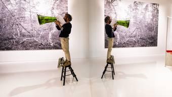 Ein Mann übt mit Flüstertüte im Ehrengast-Pavillon auf der Buchmesse für eine bevorstehende Performance. Der Raum wurde mit Spiegelflächen optisch erweitert und wirkt licht, kühl, minimalistisch.