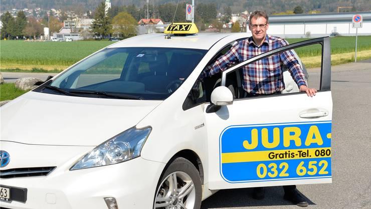 Urs Hänzi mit einem aktuellen Taxifahrzeug mit Hybridantrieb.