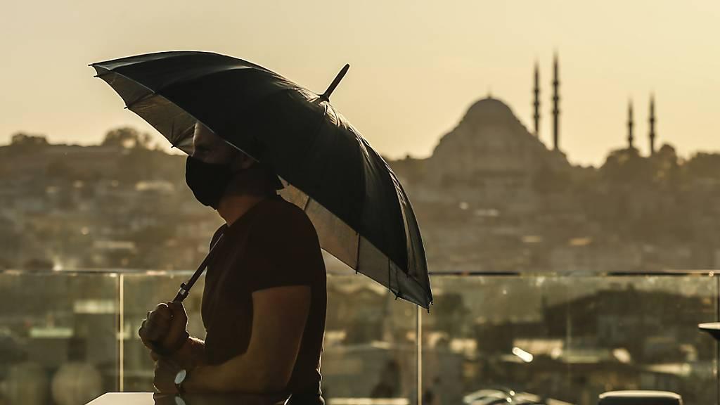 ARCHIV - Ein Tourist trägt einen Mund-Nasen-Schutz und hält einen Regenschirm während er von der Süleymaniye-Moschee über die Stadt blickt. (Archivbild) Foto: Emrah Gurel/AP/dpa