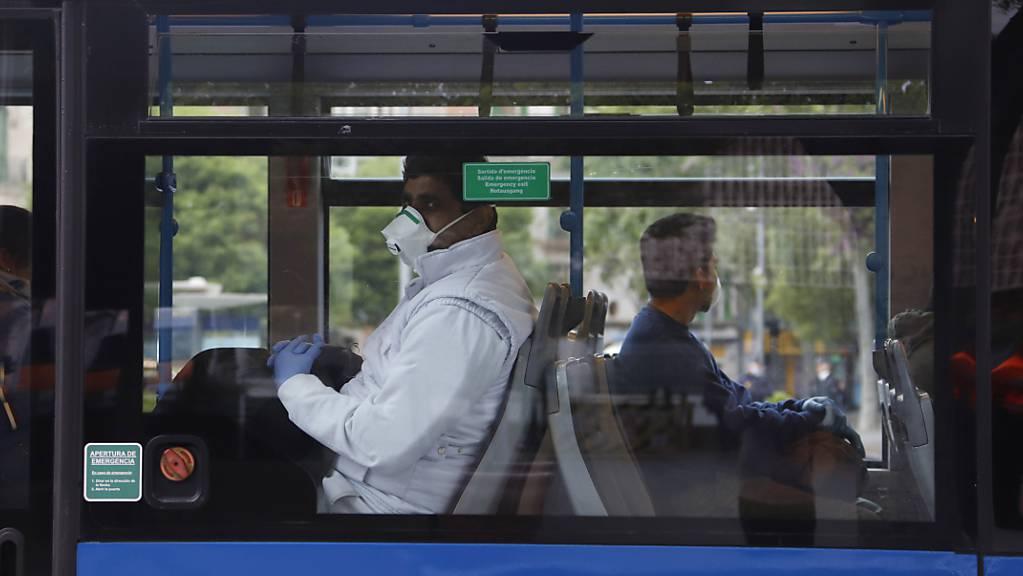 ARCHIV - Fahrgäste mit Mund-Nasen-Schutz sitzen am Bahnhof «Intermodal» in einem Bus. Zur Eindämmung von Corona-Infektionen sollen Fahrgäste in Bussen und Bahnen auf Mallorca und den anderen beliebten Ferieninseln der Balearen möglichst den Mund halten. Foto: Clara Margais/dpa