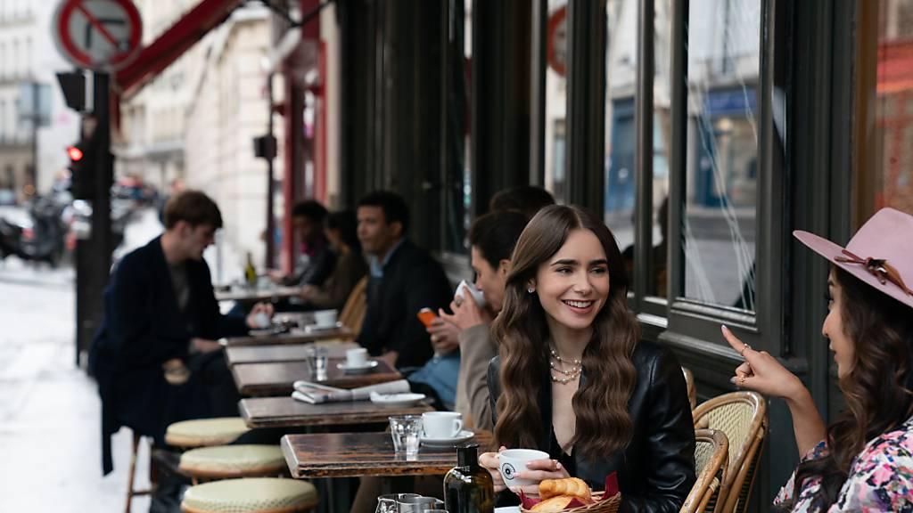 HANDOUT - Emily (Lily Collins, M) sitzt mit einer Freundin im Café - eine Filmszene aus der ersten Staffel der Netflix-Serie «Emily in Paris» (undatierte Aufnahme). In Frankreich spielende TV-Serien wie «Emily in Paris» oder «Lupin» kurbeln den Tourismus an den Schauplätzen an. Foto: Stephanie Branchu/Netflix © 2020/dpa - ACHTUNG: Nur zur redaktionellen Verwendung im Zusammenhang mit einer Berichterstattung über die Serie und nur mit vollständiger Nennung des vorstehenden Credits