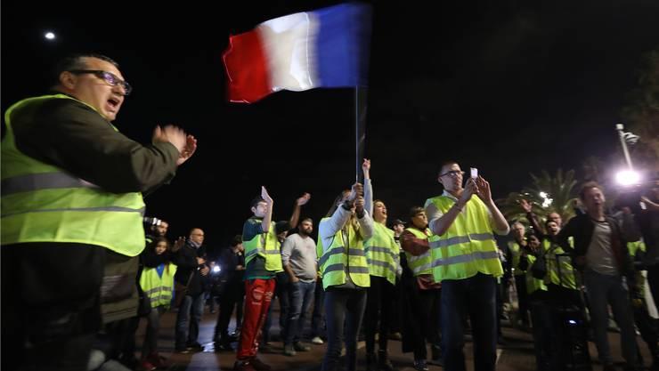 Französische Autofahrer sind wütend: Ein Demonstrant schwingt die französische Flagge während eines Protestes der «gelben Westen» («Gilets Jaunes») gegen den Anstieg der Dieseltreibstoff-Steuer.