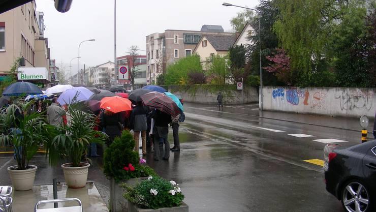 Wegend es starken Regens stehen die Gäste unter den Schrimen eng beieinander