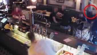 Barkeeper Jakob Heinzel bückt sich, um dem Bierkrug auszuweichen, den der Angreifer (roter Kreis rechts) geworfen hat.