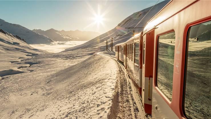 Nächster Halt: Andermatt! Der Glacier Express durch die malerische Winterlandschaft nähert sich dem Urserental.