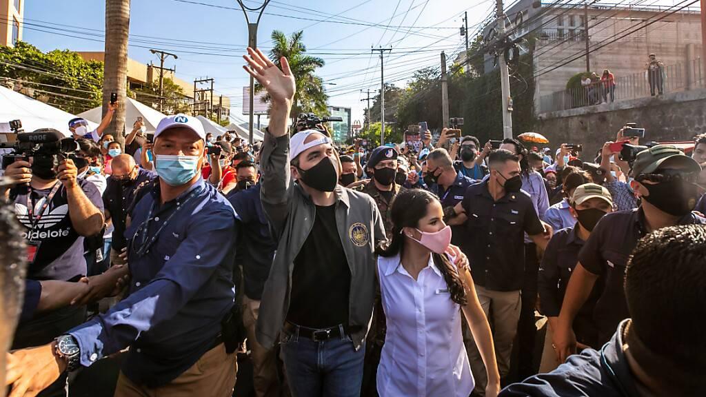 HANDOUT - Auf diesem vom Präsidentenamt von El Salvador zur Verfügung gestellten Bild winkt Nayib Bukele (M., l), Präsident von El Salvador, Anhängern zu, während er mit seiner Frau Gabriela Rodriguez (M., r) zum Wahllokal kommt. Foto: ---/Prensa Presidencia/dpa - ACHTUNG: Nur zur redaktionellen Verwendung und nur mit vollständiger Nennung des vorstehenden Credits