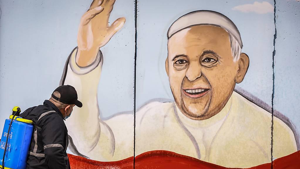 Ein Arbeiter versprüht Desinfektionsmittel an einem Wandgemälde von Papst Franziskus in Bagdad. Foto: Ameer Al Mohammedaw/dpa
