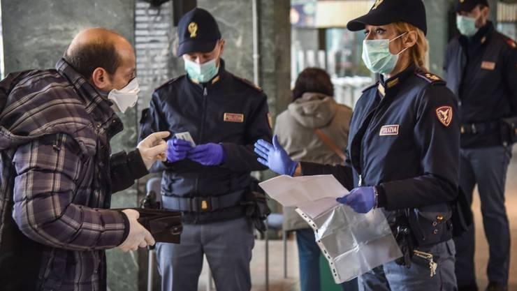Italienische Polizisten checken Reisende beim Verlassen des Bahnhofs in Mailand. EPA Fotograf: MATTEO CORNER