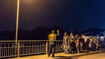 Ein Grenzpolizist stoppt Flüchtlinge auf einer Brücke zwischen Österreich und Deutschland.