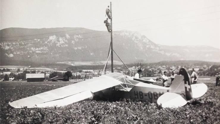 Die Piper L-4 HB-OBM aus Grenchen wurde stark beschädigt, nachdem sie bei einem Startunfall mit der Stromleitung kollidiert war. Am Mast dürften bereits Monteure der AEK am Reparieren sein.