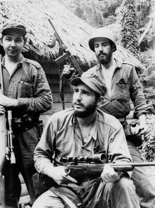 1957: Guerrilla-Chef Fidel Castro mit seinem Bruder Raul (l.) und Camilo Cienfuegos (r).