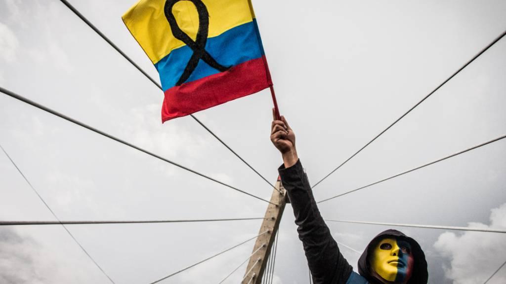 ARCHIV - Ein maskierter Demonstrant schwenkt eine Fahne während einer Kundgebung. Foto: Juan Pablo Otalvaro M/dpa