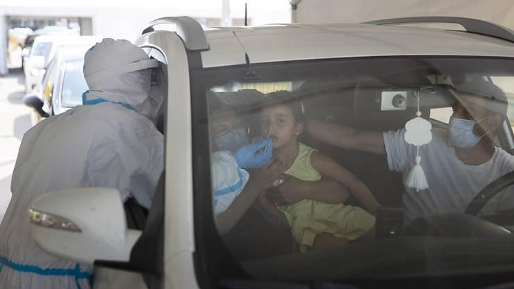 Ein medizinischer Mitarbeiter entnimmt einem Mädchen an einer Drive-Thru-Station für Covid-19-Tests einen Abstrich über die Nase. Nach einem deutlichen Anstieg von Corona-Neuinfektionen hat Israel am Montag die Beschränkungen zur Eindämmung des Virus verschärft. Foto: Sebastian Scheiner/AP/dpa