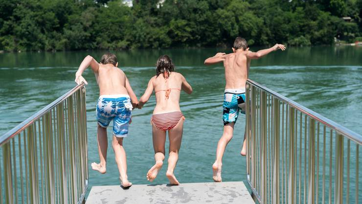 Kinder springen im Strandbad Rheinfelden in den Fluss. Abkühlung ahoi!