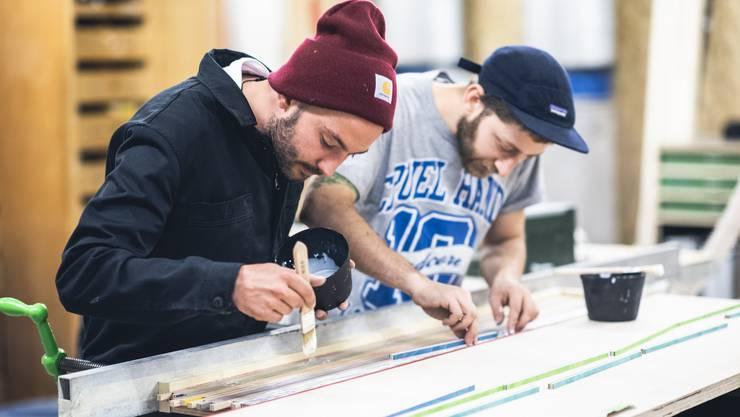 David Zuber (links) und Aron Gaspar verleimen die schmalen Streifen von zerschnittenen Skateboards.