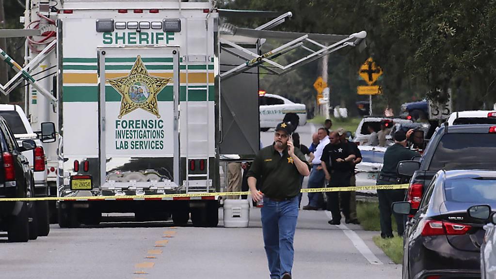 Beamte des Sheriffs von Polk County (Florida) arbeiten am Tatort einer Schießerei mit mehreren Toten. Foto: Michael Wilson/The Lakeland Ledger via AP/dpa