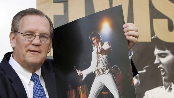 """Der Elvis-Fotograf Ed Bonja posiert am 13. Aug. 2007 in Berlin mit einem Foto des """"King of Rock 'n' Roll"""" vor einem Ausstellungsplakat. Im September 2019 ist Bonja im Alter von 74 Jahren gestorben. (Archiv)"""