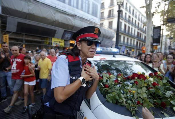 Eine Polizistin ist gerührt, nachdem Menschen auch Blumen auf das Polizeiauto legen.