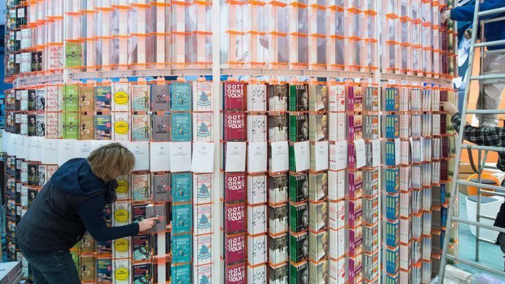 Verlagsangestellte haben am Mittwoch noch schnell die Regale gefüllt, bevor die Leipziger Buchmesse am Donnerstagmorgen eröffnet worden ist.
