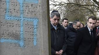 French President Emmanuel Macron, right, visits the vandalized Jewish cemetery in Quatzenheim, eastern France, Tuesday Feb. 19, 2019. French residents and public officials from across the political spectrum geared up Tuesday for nationwide rallies against anti-Semitism following a series of anti-Semitic acts, including the swastikas painted on about 80 gravestones at the Jewish cemetery overnight. (Frederick Florin, Pool via AP)