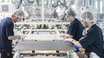 Mitarbeitende bearbeiten Solarwafers: Die Grünen wollen nachhaltige Innovationen in Schweizer Firmen fördern (Symbolbild).