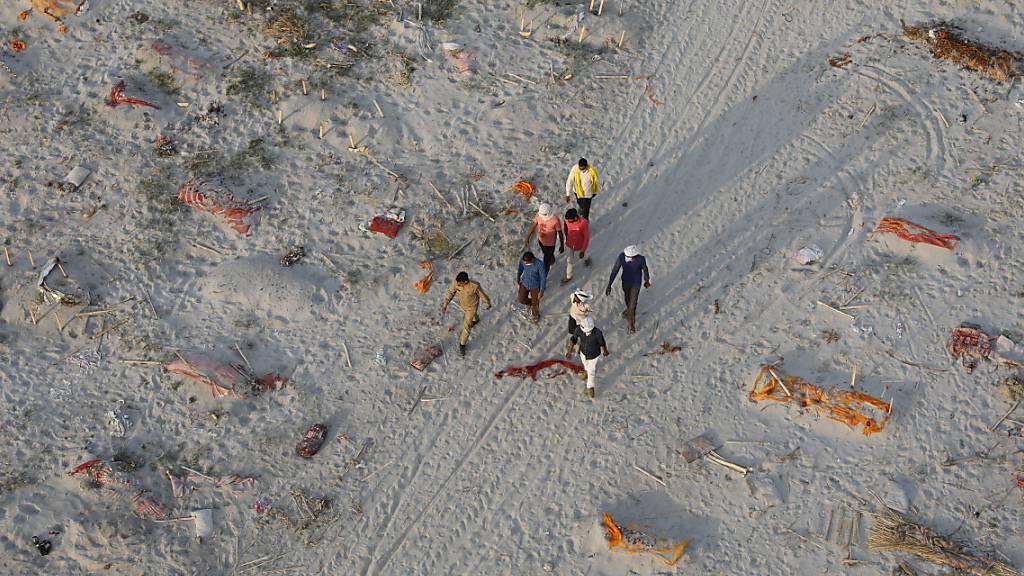 Leichen von mutmaßlichen Opfern des Coronavirus liegen in flachen Gräbern in einem Krematorium am Ufer des Ganges. Foto: Rajesh Kumar Singh/AP/dpa