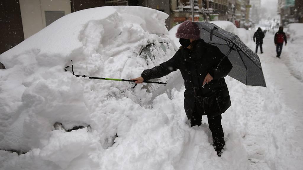 Eine Frau in Madrid befreit ihr Auto von einer hohen Schneeschicht. Foto: Andrea Comas/AP/dpa