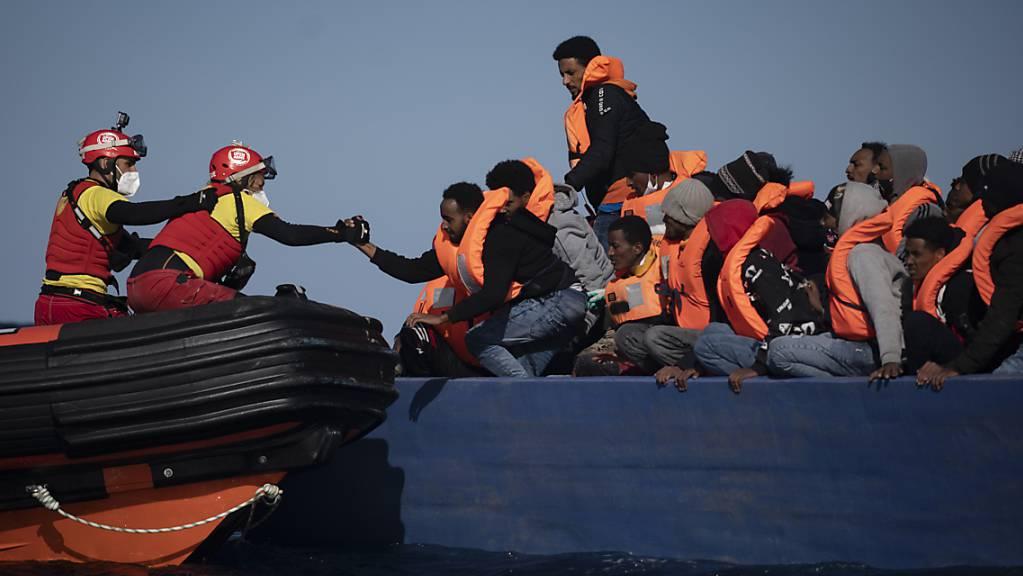 ARCHIV - Migranten aus Eritrea, Ägypten, Syrien und dem Sudan werden an Bord eines Holzbootes im Mittelmeer etwa 110 Meilen nördlich von Libyen darauf, von Helfern der spanischen NGO «Open Arms» unterstützt. (Illustration zu dpa: «Hilfsorganisation Open Arms rettet mehr als 30 Bootsmigranten») Foto: Joan Mateu/AP/dpa