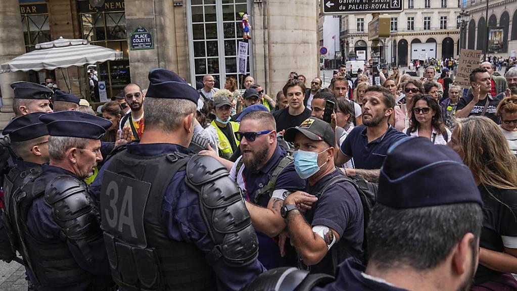 Demonstranten stehen bei einem Protest gegen den neuen Gesundheitspass in Paris Polizisten gegenüber. Foto: Michel Euler/AP/dpa