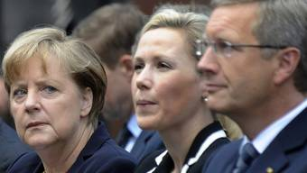 Angela Merkel(l) steht hinter Bundespräsident Wulff (Archiv)