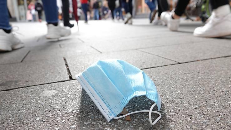 In der Fußgängerzone der Kölner Innenstadt gehen viele Menschen an einer auf dem Boden liegenden Mund-Nasen-Bedeckung vorbei. .Erstmals seit April wurden in Deutschland mehr als 5000 neue Corona-Infektionen innerhalb eines Tages gemeldet. Foto: Weronika Peneshko/dpa