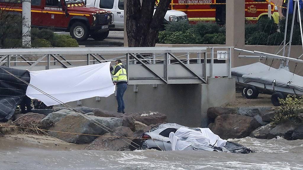 Rettungskräfte bergen die Leichen von zwei Menschen aus einem Auto, das von einem über die Ufer getretenen Fluss mit ins Meer gerissen wurde.