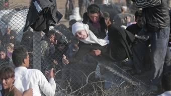 Syrische Flüchtlinge versuchen den Grenzzaun zur Türkei zu überwinden