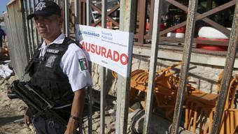 """Ein mexikanischer Polizist bewacht den Ausgang des """"Blue Parrot""""-Nachtklubs in Playa del Carmen, wo am frühen Montagmorgen mindestens fünf Menschen getötet wurden."""