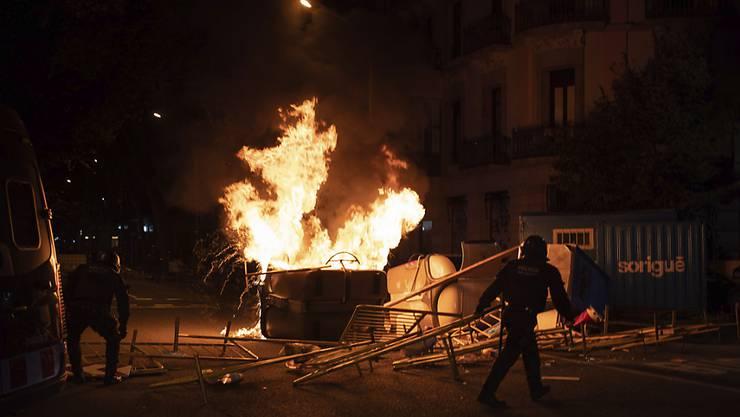 Polizisten entfernen Barrikaden während einer Kundgebung gegen die Enthebung des katalanischen Regionalpräsidenten Torra. Foto: Felipe Dana/AP/dpa