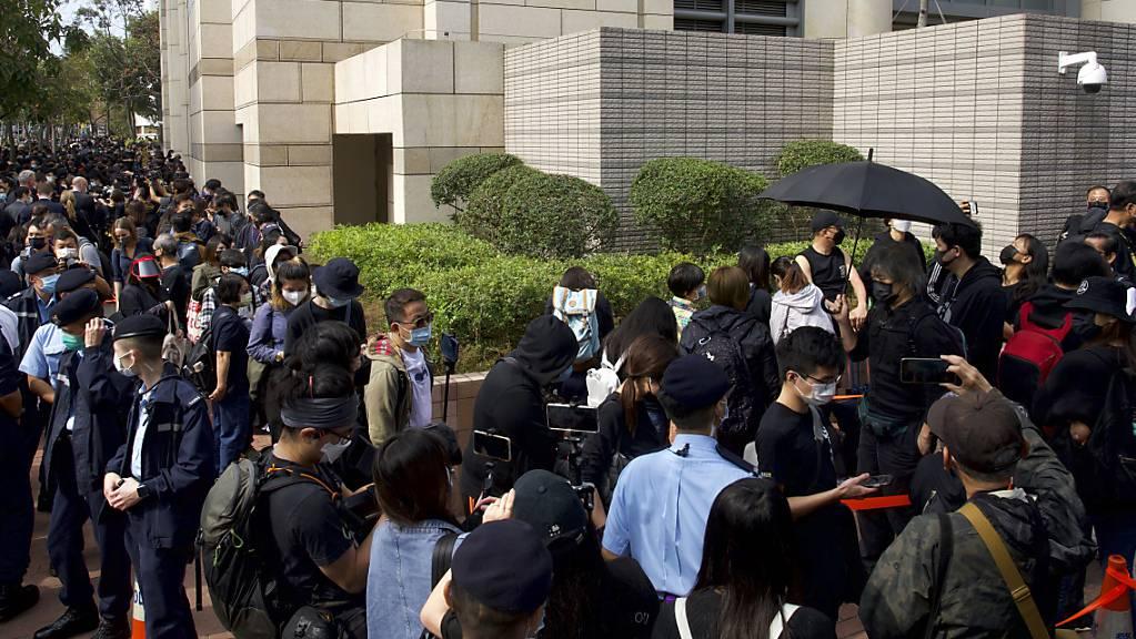Unterstützer warten vor einem Gericht und versuchen, zu einer Anhörung zu gelangen. Foto: Vincent Yu/AP/dpa