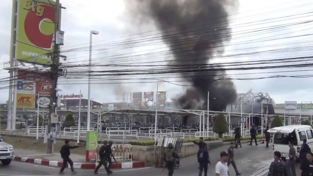 In this image made from video, smoke rises from an exploded vehicle outside a popular shopping center in Pattani province, southern Thailand, Tuesday, May 9, 2017. Suspected insurgents detonated a car bomb Tuesday outside the busy shopping center wounding more than 50 people in a huge blast that ripped the building apart and sent people running for their lives. (AP Photo)