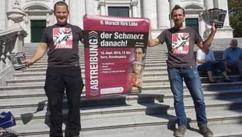Tobias Steiger und Marcel Eggers mit einem Plakat und Flugblättern zum Marsch.