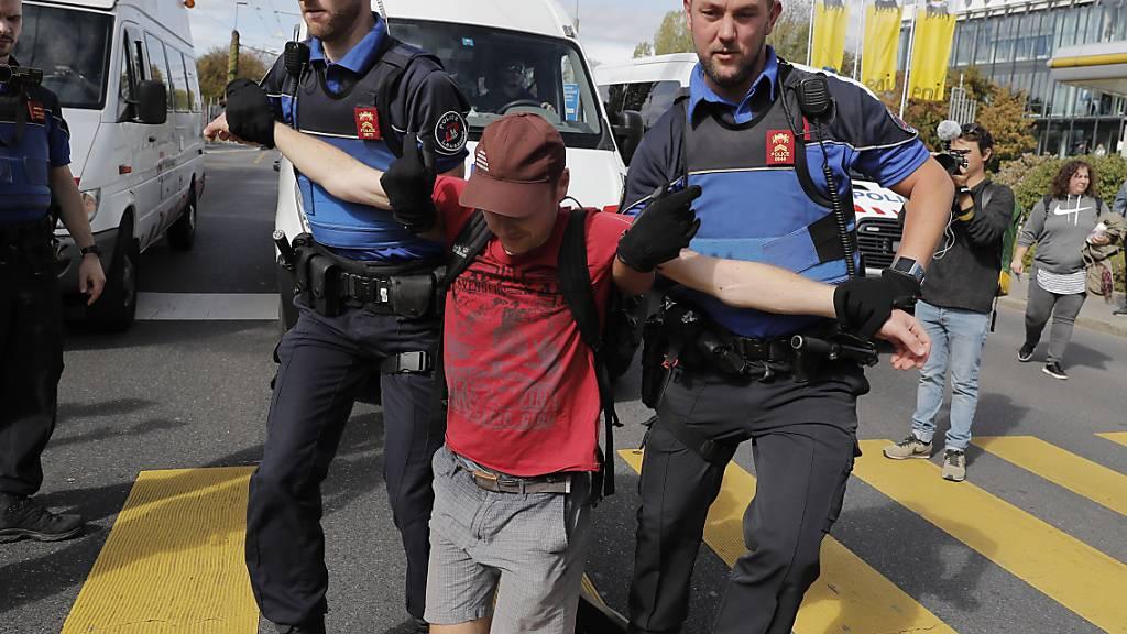 Ein Teilnehmer der Klimademonstration in Lausanne wird von der Polizei weggetragen.