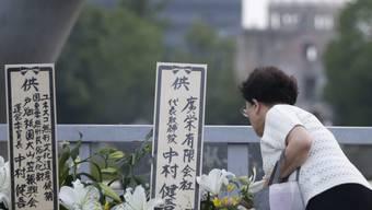 Eine Japanerin legt am 71. Jahrestag Blumen nieder für die Opfer des Atombombenangriffs von Hirsoshima. Im Hintergrund der Kenotaph, der an den Abwurf der amerikanischen Atombombe 1945 erinnert.