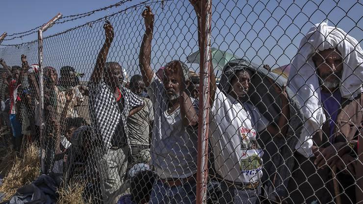 Geflüchtete Menschen aus der Region Tigray warten im Sudan auf Decken, die von dem UN-Flüchtlingshilfswerk UNHCR ausgegeben werden. Foto: Nariman El-Mofty/AP/dpa