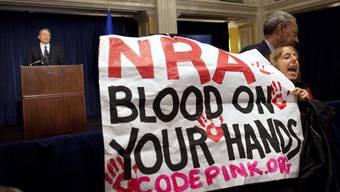 Eine Aktivistin hält während eines NRA-Statements ein Transparent in die Höhe, welches die Waffenlobby stark kritisiert