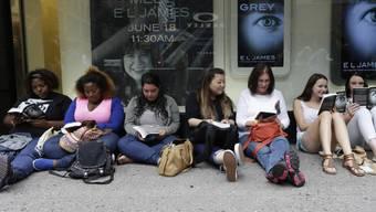 """Fans """"versüssen"""" sich die Wartezeit auf ein Autogramm mit dem neu erworbenen """"Grey""""."""